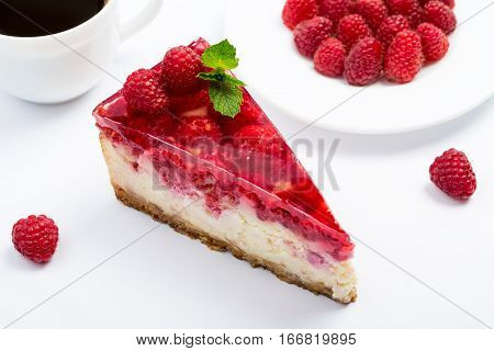 Raspberry cheesecake with coffee on a white background.