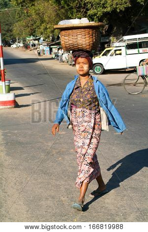 Thazi Myanmar - 11 January 2010: Woman carrying products in a basket on her head walking on the street of Thazi on Myanmar