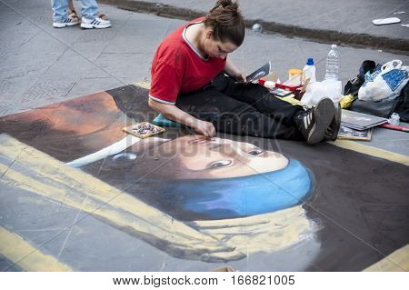 Florence Italy - may 17.2015: The young girl the artist draws the copy of a portrait on the sidewalk.