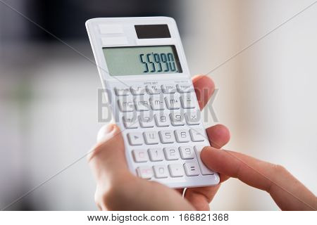 Close-up Of A Person Doing Calculation On Calculator