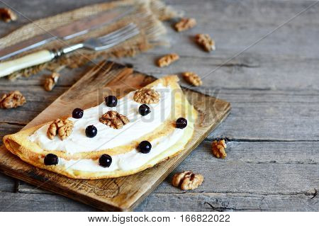 Egg omelette with sweet filling. Home omelette with soft cheese and walnuts. Fork, knife, raw shelled walnuts on a wooden background with empty place for text. Easy kids breakfast recipe. Closeup