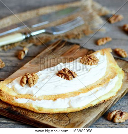 Stuffed omelette on a wooden board. Home fried omelette with soft cheese and walnuts. Cutlery, shelled walnuts on a wooden table. Breakfast egg recipe. Rustic style. Closeup