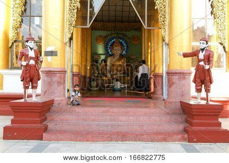 Yangon Myanmar - 9 January 2010: Boy sitting in the area of the Shwedagon Pagoda in Yangon on Myanmar