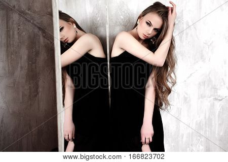 Young Girl With Long Beautiful Hair And Smoky Eyes Wearing Black Maxi Evening Dress Posing With A Mi