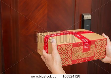 ZhongshanChina-January 25 2017:male courier from JD.com delivering a parcel with Chinese New Year things.January 28 is the 1st day of year Rooster and JD.com is one of the biggest online shopping mall in China.