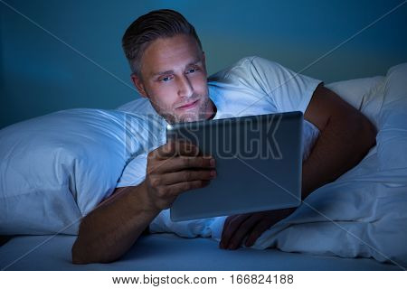 Man Lying On Bed Looking At Illuminated Digital Tablet