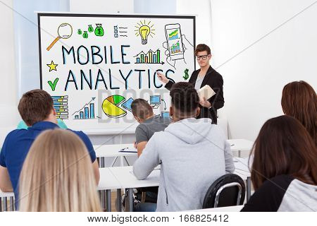 Male Teacher Explaining The Concept Of Mobile Analytics To Students In Classroom