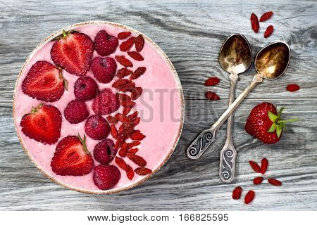 Pink acai maca powder smoothie bowl topped with sliced strawberries raspberries and goji berries. Flat lay copy space. Valentines Day superfood aphrodisiac meal