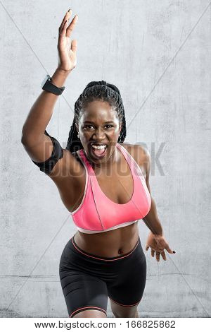 Medium shot of black female athlete in take off position. Young woman with vigorous face expression with hands in air against grey concrete background.