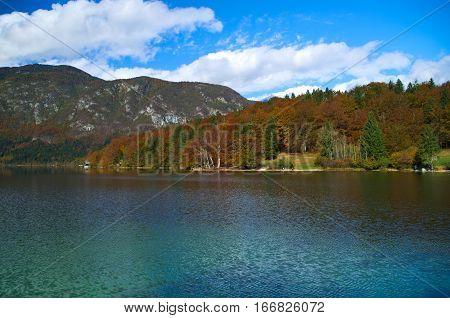 Autumn view of the stone bridge and the Church of St. John the Baptist at Lake Bohinj (Bohinjsko jezero), Slovenia