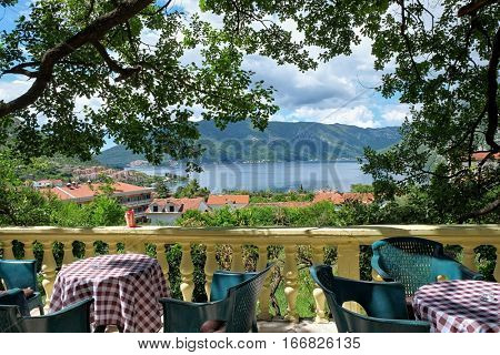 RISAN, MONTENEGRO - YULY 17, 2016: picturesque view, framed with oak fronds, on Kotor Bay from a terrace with balustrade