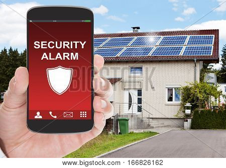 Close-up Of Person With Security Alarm On A Smartphone Outside The House