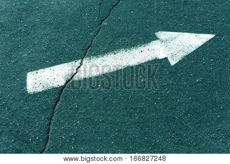 White Arrow On Cyan Toned Asphalt Surface.