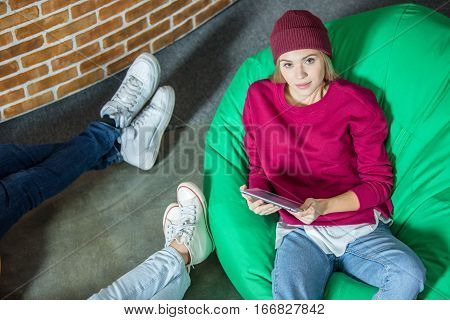Top view of young woman sitting in bean bag chair and using digital tablet