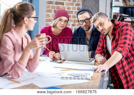 Group of young male and female designers working at project with blueprints and laptop