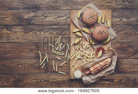 Fast food dish top view. Appetizing meat burgers, potato chips and wedges, hot dog sausage. Takeaway composition. French fries, hamburger and sauces on wood with copy space. Menu or recipe mockup