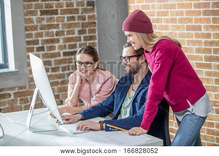 Three young smiling businesspeople working with computer