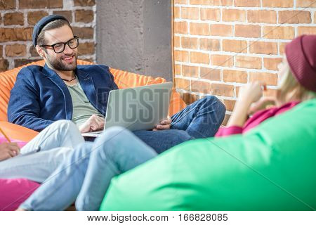 Handsone smiling man working on laprop while sitting in bean bag chair