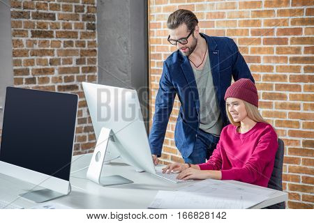 Young stylish man and woman working on computer in office