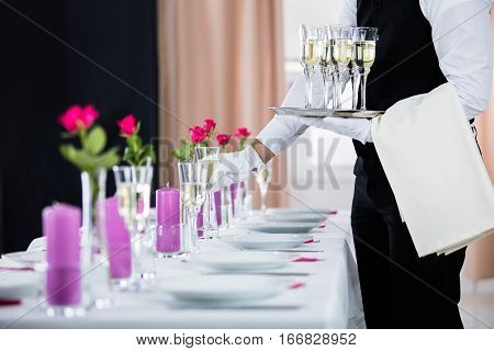 Waiter Serving Champagne On Banquet Table At Restaurant