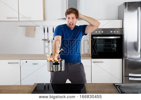 Young Surprised Man Holding Utensil On Fire In Kitchen