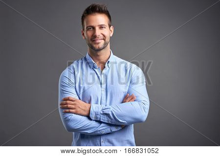 A confident handsome young man standing in front of a grey background in a studio