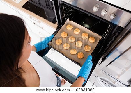 High Angle View Of Young Woman Baking Cookies In Oven At Home