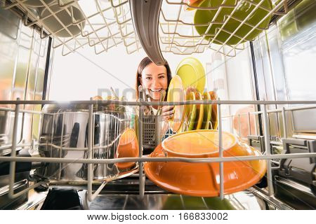 Young Happy Woman Arranging Plates In Dishwasher