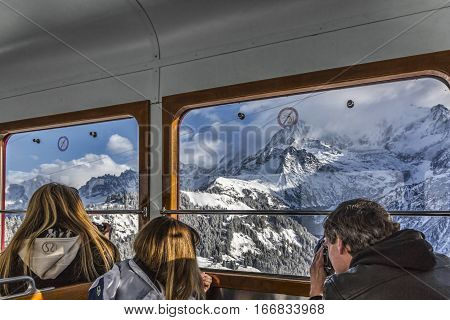 Motivon, France - December 30 2017: Unidentified tourists looking through the window to the Glacier of Bionnassay from the Tramway of Mont Blanc on the way to Col de Voza on December 30 2017.