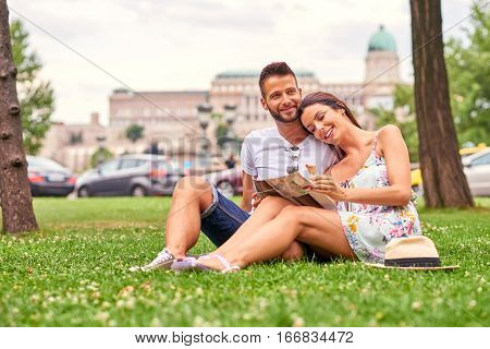 A beautiful young couple are siting in the grass having an ice-cream with the Castle in background in Budapest, Hungary.