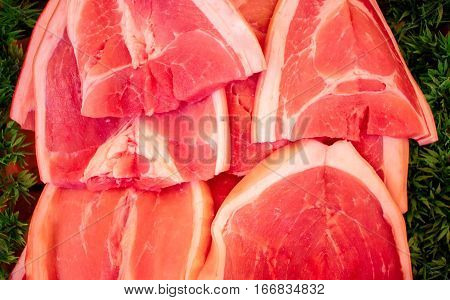 Red meat on a green background. Tasty fresh meat sliced on supermarket display. Protein nutrition or cooking ingredient. Beef or pork red meat. Raw meat closeup photo for recipe illustration or banner