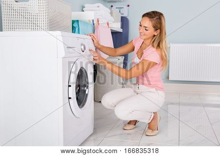 Young Happy Woman Using Washing Machine In Utility Room