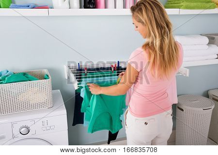 Woman Hanging Wet Clean Cloth To Dry On Clothes Line At Laundry Room