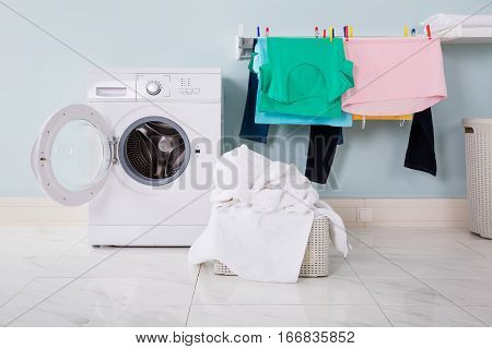 Empty Washing Machine With Pile Of Dirty Cloth In The Basket At Laundry Room