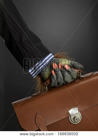 Hairy hand holding briefcase against gray graduated background