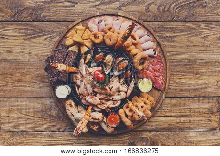 Seafood and meat platter. Mediterranean cuisine restaurant food, fried calamari rings, king prawns, mussels, oysters, shellfish delicacy, top view on wood table background. Catering, banquet table