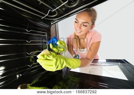 Smiling Cleaning Service Professional Woman Cleaning Inside The Oven With Spray Bottle And Sponge