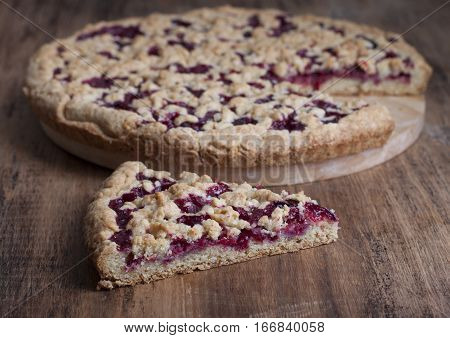 Sand pie with cranberries on a wooden board and a piece of pie on the table