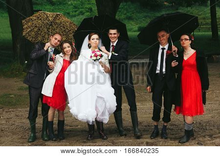 Newyweds, Bridesmaids And Groomsmen Pose Under Umbrella In Gumboots