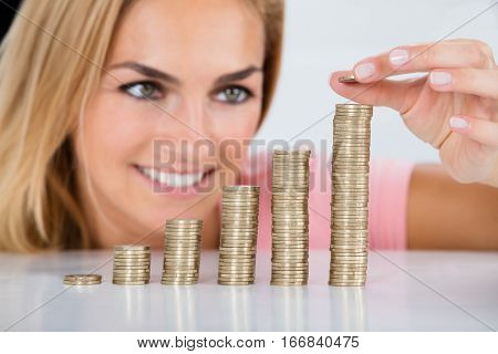Young Happy Woman Inserting Coin On The Stacked Of Coins On Desk At Home