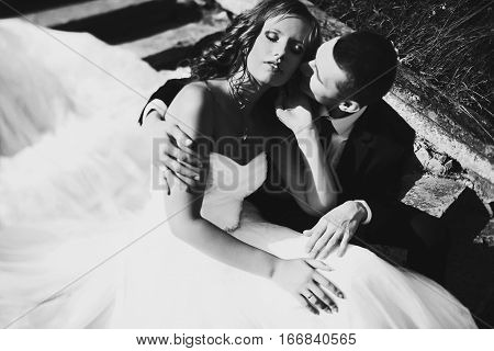 Sun Illuminates Bride's Face While She And Fiance Sit On The Stone Footsteps