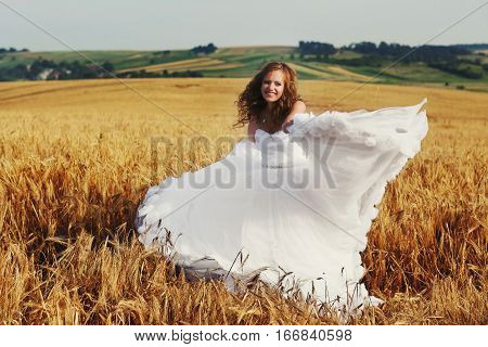 Happy bride sways her dress standing on the field