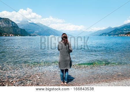 Back View Of Young Lonely Woman Relaxing On Como Lake In Italy