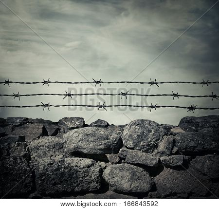 Masonry stone wall fence of a prison with barbed metallic wire above.