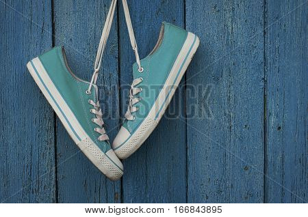Turquoise youth sneakers hanging on a nail blue shabby wooden background