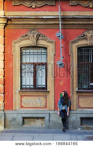 Portrait of a young long haired cute brunette woman in denim jacket and pantsthoughtfully leaning against the wall of an old St. Petersburg building with bas-reliefs above the Windows