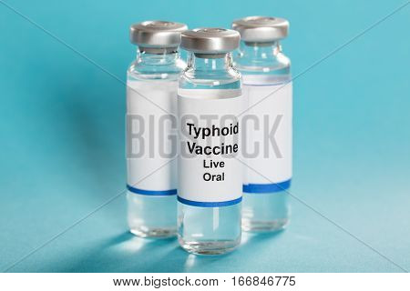 Three Vials Of Typhoid Vaccine Over Turquoise Background