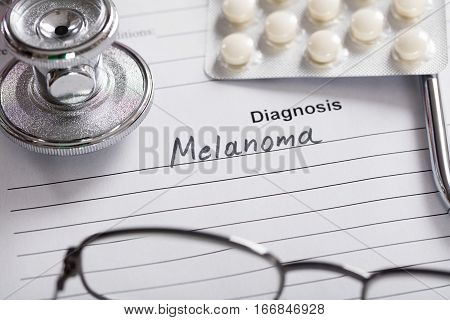 Close-up Of Text Melanoma On Piece Of Paper With Stethoscope And Medicine