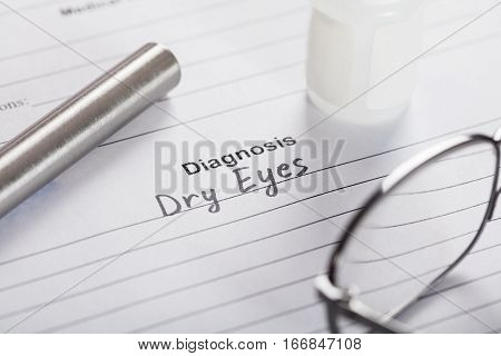 Close-up Of Text Diagnosis Dry Eyes On Piece Of Paper With Glasses And Medicine