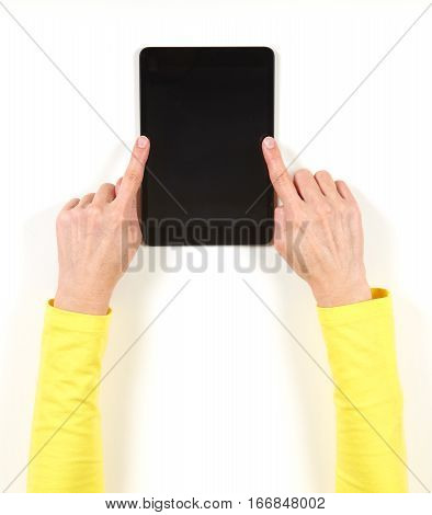 Hands in yellow jacket and black tablet on white background